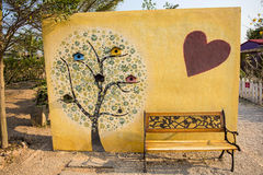 Art tree painting on cement wall and yellow park bench Stock Image