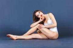 Art und Weisebaumuster, das im Studio aufwirft Geeignete Frau im Badeanzug Schöne und gesunde Frau, die über blauem Hintergrund a Lizenzfreie Stockfotografie