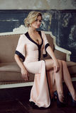 Art und Weisebaumuster mit dem blonden Haar Junge attraktive Frau, stationierend auf dem Sofa, Weinleseart Stockfotografie