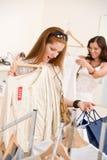 Art und Weiseeinkaufen - wählen junge Frau zwei Kleidung Lizenzfreies Stockbild