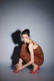 Art und Weiseeintragfaden einer jungen Frau in einem braunen Kleid Lizenzfreies Stockbild