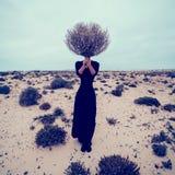 Art und Weisefoto Mädchen in der Wüste mit toten Zweigen eines Blumenstraußes Stockfotografie