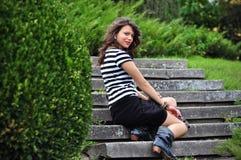 Art- und Weisemädchen, das auf Treppen im Park sitzt Stockbilder