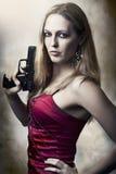 Art und Weiseportrait der reizvollen Frauenholdinggewehr Stockfoto