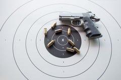 Art von 45 Kugeln auf Bullaugenziel mit unscharfer Pistole Stockbild