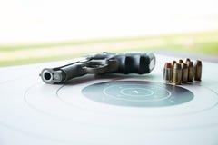 Art von 45 Kugeln auf Bullaugenziel mit unscharfer Pistole Stockbilder
