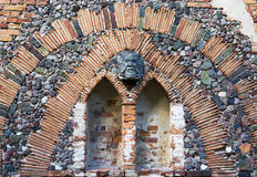 The art wall with the mascaron in Arkadia park in Poland. The Arkadia park is the known romantic English landscape garden in Poland. The wall fragment belong to stock photo
