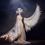 Art Woman ängel med vingar i lyxig lång klänning och sagolik huvudbonad Flickafågel med lysande vingar som poserar på mörk bakgru Arkivbild