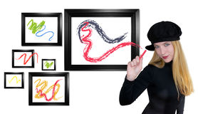 Art Woman Painting Out of the Box. A blond artistic woman is painting colorful swirls on black frames on a white isolated background. She is wearing a black hat Stock Photos