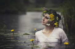 Art Woman with wreath on her head in a swamp in the woods. Wet w Stock Images