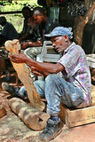 Art workshop outdoors woodcarver carves. Namanga, Tanzania - February 9, 2008: Dark skinned middle-aged African, master wood carving works of art workshop, under Stock Photos