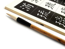 Art of writing chinese calligraphy. An image of a chinese calligraphic writing brush beside a book for learning about calligraphy.  Open page of book shows ways Royalty Free Stock Image