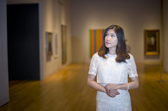 Art. Young  woman standing in an art gallery Stock Photography