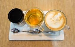Arte atrasada do café na garrafa do copo e do açúcar e no copo de chá na placa branca na tabela de madeira imagem de stock royalty free