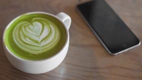 Arte calda del latte del tè verde sul negozio di legno del caffè della tavola Fotografia Stock Libera da Diritti
