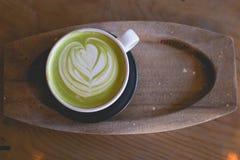 Arte caliente del latte del té verde en tienda de madera del café de la tabla Fotografía de archivo