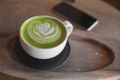Arte caliente del latte del té verde en tienda de madera del café de la tabla Imágenes de archivo libres de regalías