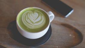 Arte caliente del latte del té verde en tienda de madera del café de la tabla Fotos de archivo