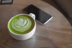Arte caliente del latte del té verde en tienda de madera del café de la tabla Foto de archivo libre de regalías