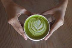 Arte caliente del latte del té verde a mano en tienda del café de la tabla Imágenes de archivo libres de regalías
