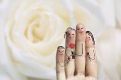 Arte conceptual del finger de la familia El padre, el hijo y la hija están dando a flores su madre Imagen común Imagenes de archivo