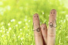 Arte conceptual del finger de pascua Los pares con el conejito están sosteniendo los huevos pintados Imagen común Imagenes de archivo