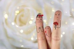 Arte concettuale del dito della famiglia Il padre ed il figlio stanno dando a fiori sua madre Immagine di riserva Immagine Stock