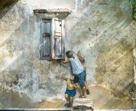 arte da rua 3D na parede A pintura dos meninos está jogando perto das janelas foto de stock royalty free