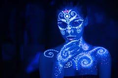 Arte de cuerpo en el cuerpo y la mano de una muchacha que brilla intensamente en la luz ultravioleta imágenes de archivo libres de regalías