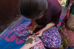 Arte de la alheña: manos de pintura de la muchacha local con color tradicional negro en una casa india imagen de archivo libre de regalías