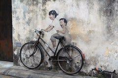 Arte de la calle en Penang, niños en la bicicleta Imagen de archivo