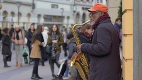 Arte de la calle, hombres del negro del ejecutante del músico viejos que juegan en el instrumento musical para la gente de los tr almacen de metraje de vídeo