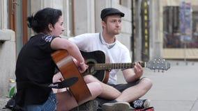 Arte de la calle, individuo del mendigo con la muchacha que toca el instrumento musical que se sienta en el asfalto al aire libre almacen de video