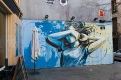 Arte de la calle de una mujer joven que cubre su cara con un brazo en el th imágenes de archivo libres de regalías