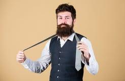 Arte de la masculinidad El inconformista barbudo del hombre intenta hacer el nudo Maneras diferentes de atar nudos de la corbata  imagen de archivo