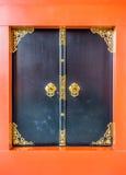 Arte de portas de madeira pretas com teste padrão floral dourado e quadro alaranjado Fotografia de Stock