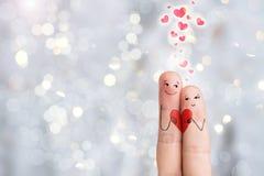Arte del dito Gli amanti sta tenendo il cuore rosso Bokeh Immagine di riserva Immagini Stock Libere da Diritti