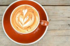 Arte del latte del café en la taza marrón en la tabla de madera fotos de archivo libres de regalías