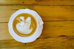 Arte del latte del caffè sulla tazza di legno della tavola Fotografia Stock