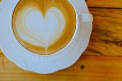 Arte del latte del caffè sulla tazza di legno della tavola Fotografie Stock