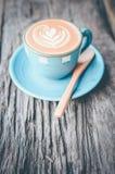 Arte del Latte, taza de café azul en fondo de madera Foto de archivo