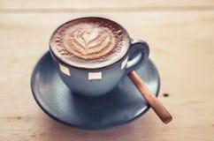Arte del Latte, taza de café azul en fondo gris Imágenes de archivo libres de regalías