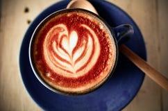 Arte del Latte, taza de café azul en fondo gris Foto de archivo