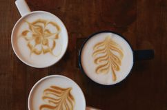 Arte del Latte - tres tazas en el café en fondo de madera oscuro Fotografía de archivo libre de regalías
