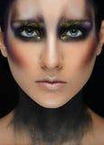 Arte del maquillaje y tema modelo hermoso: muchacha hermosa con un maquillaje creativo negro-y-púrpura y colores oro en un backgr imagen de archivo