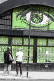 Arte della via a Londra Due giovani pantaloni a vita bassa sotto una parete con il grande occhio Fotografia Stock