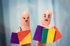 Arte do dedo de um par com sacos de compras O homem é infeliz porque era cansado da compra fotografia de stock royalty free
