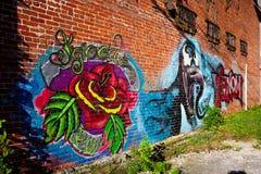 Arte dos grafittis de Rosa e de veneno na parede de tijolo imagem de stock royalty free