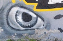Arte dos grafittis na parede da rua na cidade que mostra o olho pintado no fundo concreto cinzento foto de stock