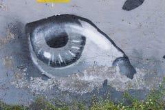 Arte dos grafittis na parede na rua da cidade que mostra o olho pintado no fundo concreto cinzento imagem de stock royalty free